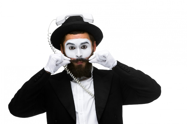 Mann im bild pantomime, der einen hörer hält.