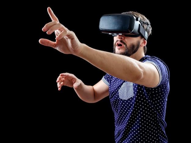 Mann im blau gepunkteten t-shirt, das 3d-headset der virtuellen realität trägt