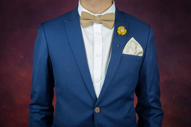 Mann im blauen anzug bowtie, brosche, taschentuch