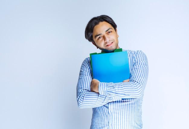 Mann im blauen hemd, das grünen berichtsordner hält. foto in hoher qualität