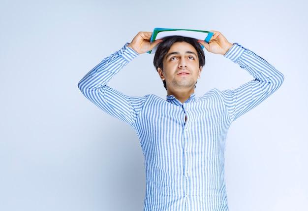 Mann im blauen hemd, das grünen berichtsordner über seinem kopf hält. foto in hoher qualität