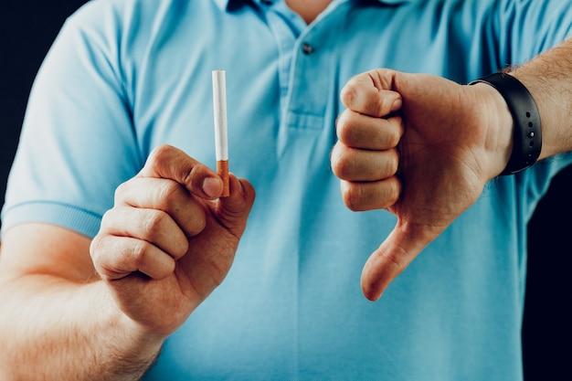 Mann im blauen hemd, das rauchen gestikuliert, ist nahaufnahme schlecht
