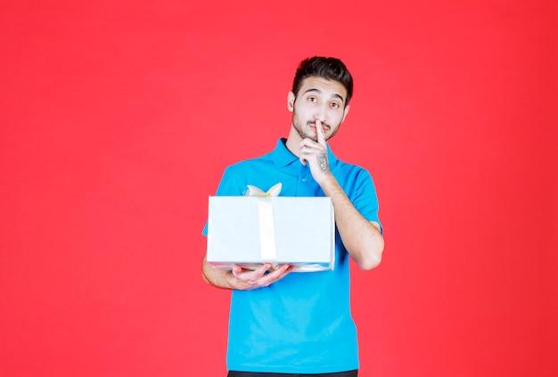 Mann im blauen hemd hält eine silberne geschenkbox und sieht überrascht und nachdenklich aus