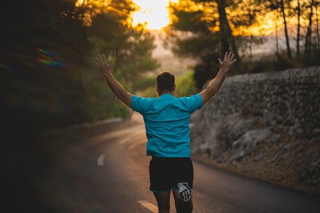 Mann im blauen hemd läuft mit den armen, die auf straße während des sonnenuntergangs angehoben werden