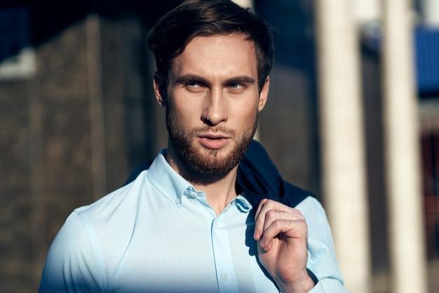 Mann im blauen hemd mit jacke auf schulter auf straße nahe gebäude