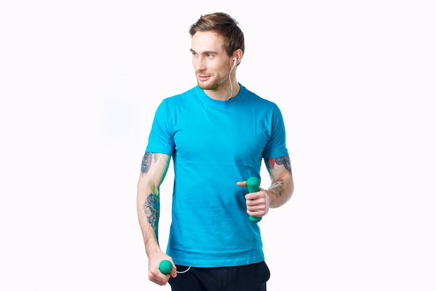 Mann im blauen t-shirt mit hanteln im hand-tattoo-fitness-training