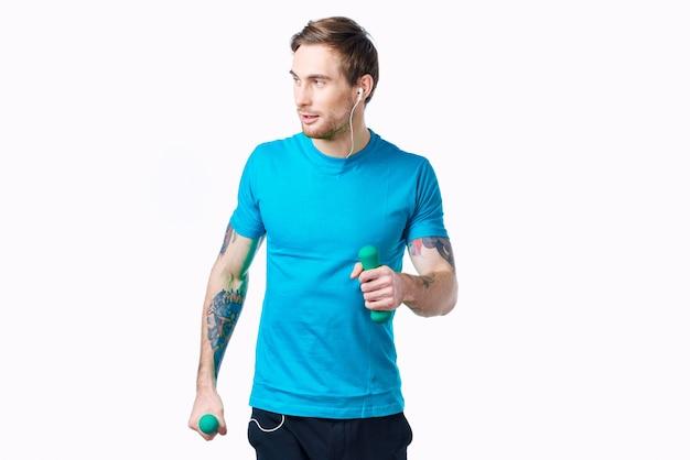 Mann im blauen t-shirt mit hanteln in der hand tattoo-fitness-workout