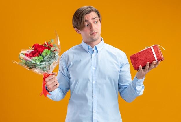Mann im blueshirt, der blumenstrauß der roten rosen und gegenwart hält, verwirrt verwirrt mit zweifeln valentinstagkonzept steht über orange wand