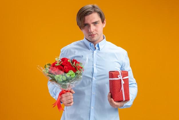 Mann im blueshirt, der blumenstrauß von roten rosen und gegenwart hält, die kamera betrachten, die selbstbewusstes valentinstagkonzept steht, das über orange wand steht