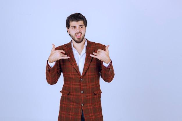Mann im braunen blazer, der flirtet und rufhandzeichen macht.