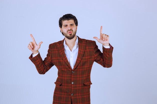 Mann im braunen blazer, der handsymbole macht und tanzt.