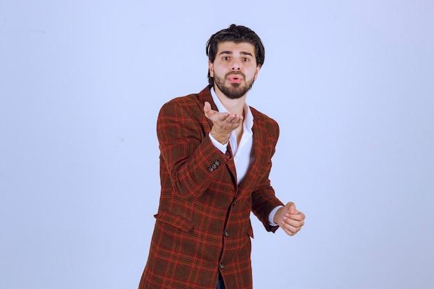 Mann im braunen blazer, der jemanden grüßt.