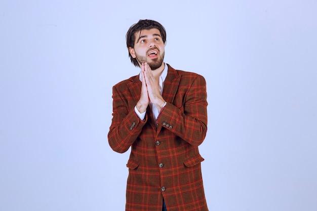 Mann im braunen blazer, der seine hände vereinigt und betet.
