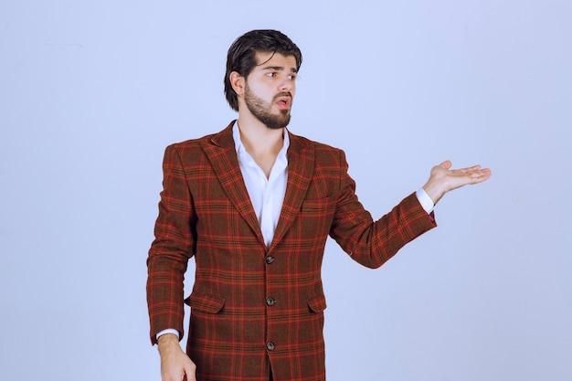 Mann im braunen blazer zeigt nach rechts und spricht.