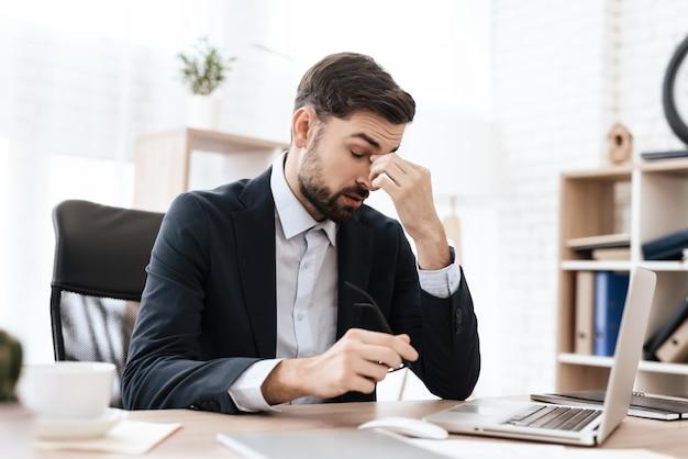Mann im büro sitzt und hält seinen kopf in den schmerz.