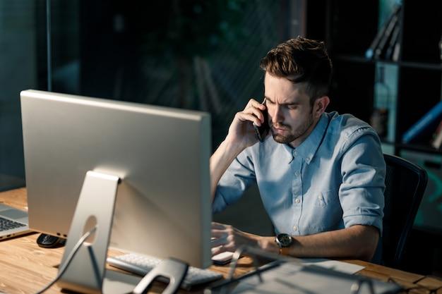 Mann im büro überarbeitet und spricht am telefon