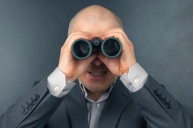 Mann im business-anzug schaut durch ein fernglas. ziele in einem erfolgreichen geschäft.
