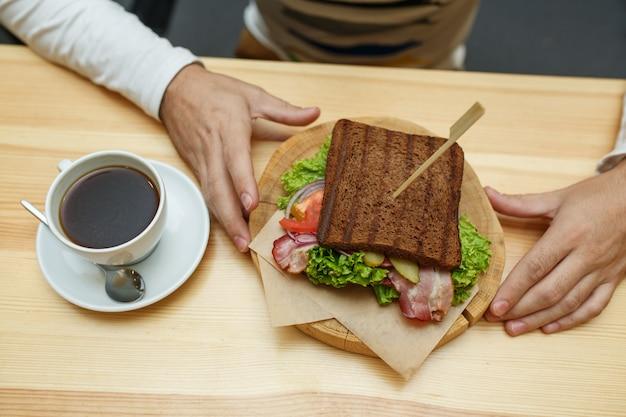 Mann im café nehmen sein bestellungssandwich und -kaffee