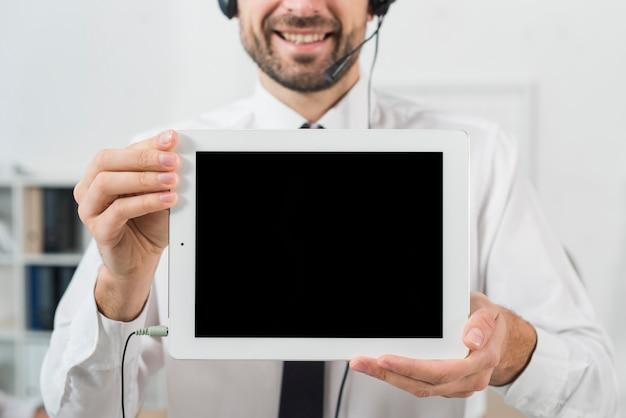 Mann im callcenter, das tablette zeigt