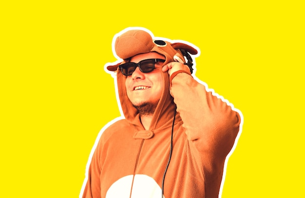 Mann im cosplay-kostüm einer kuh auf gelbem hintergrund. kerl in der tierpyjamanachtwäsche. lustiges foto mit partyideen. disco-retro-musik.