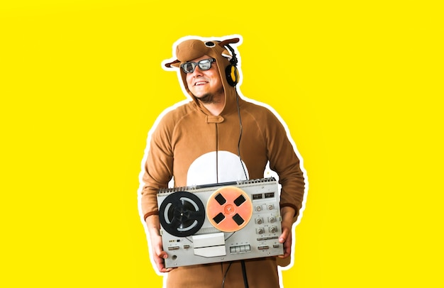 Mann im cosplay-kostüm einer kuh mit reel-tonbandgerät isoliert auf gelbem hintergrund. kerl in der tierpyjamanachtwäsche. lustiges foto mit partyideen. disco-retro-musik.