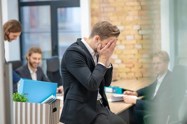 Mann im dunklen anzug, der sein gesicht mit den händen bedeckt, die am tisch in den büroangestellten dahinter sitzen