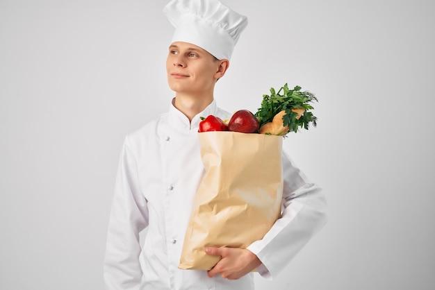 Mann im einheitlichen paket der köche mit lebensmitteln, die restaurantarbeit kochen