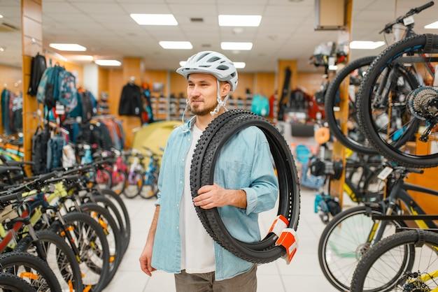 Mann im fahrradhelm hält fahrradreifen, einkaufen im sportgeschäft. extremer lebensstil der sommersaison, aktives freizeitgeschäft, kunden, die fahrradausrüstung kaufen