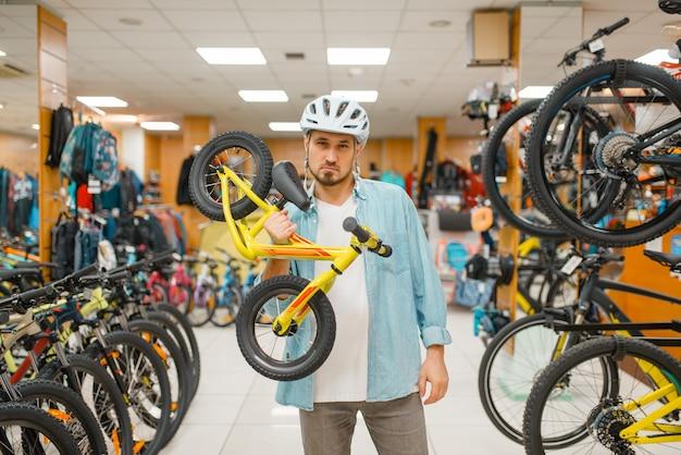 Mann im fahrradhelm hält kinderfahrrad, einkaufen im sportgeschäft. extremer lebensstil in der sommersaison, aktives freizeitgeschäft, kaufzyklus für kunden und ausrüstung für familienfahrten