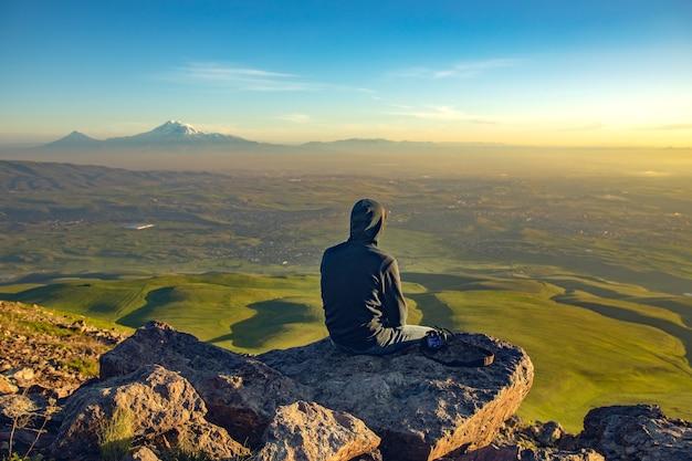 Mann im felsen und im ararat berg am sonnenuntergang