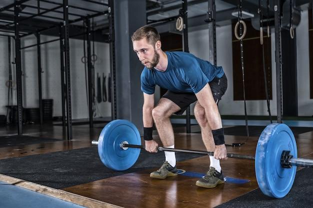 Mann im fitnessstudio. gewichtheben