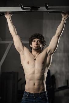 Mann im fitnessstudio machen pull-up. bodybuildertraining in der turnhalle