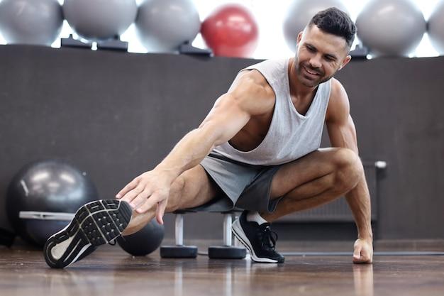 Mann im fitnessstudio macht dehnübungen auf dem boden.