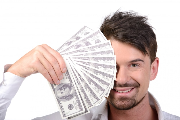 Mann im formalwear, das geld bei der stellung auf weiß hält.