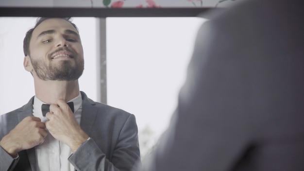 Mann im formellen geschäftsanzug oder im bräutigamkostüm, das sich in der umkleidekabine anzieht und sich auf arbeit, verlobung oder hochzeitszeremonie vorbereitet