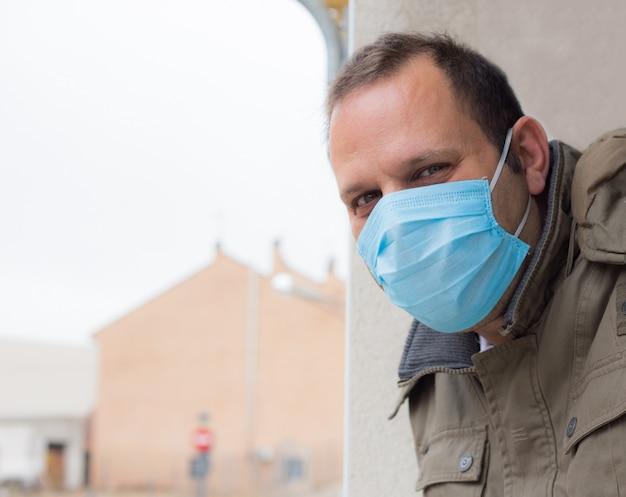 Mann im freien, der gerade mit wegwerfbarer gesichtsmaske schaut