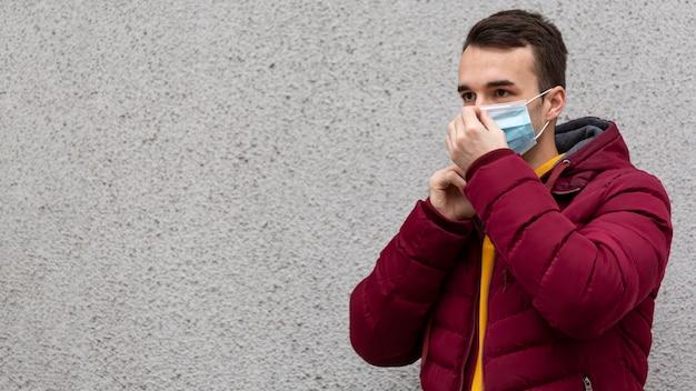 Mann im freien, der medizinische maske mit kopienraum trägt