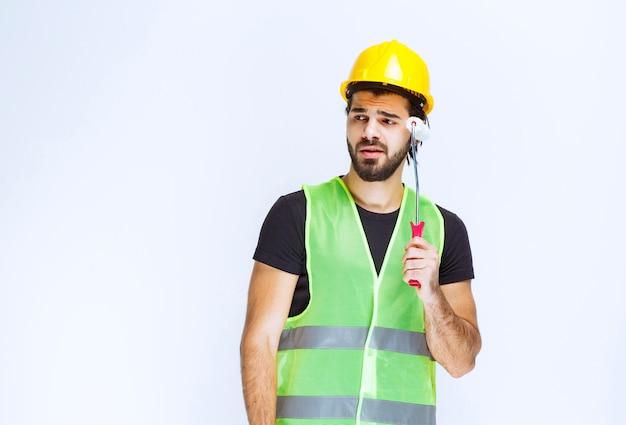 Mann im gelben helm, der eine ordnungsrolle hält und denkt.
