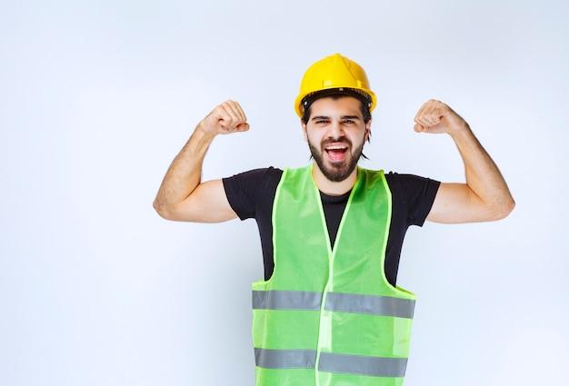 Mann im gelben helm, der seine armmuskeln zeigt.