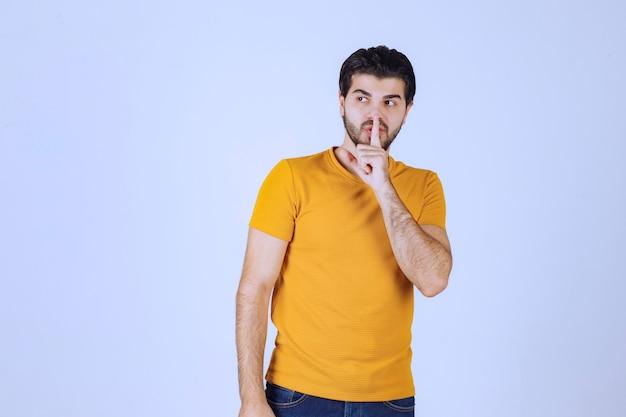 Mann im gelben hemd bittet um stille.
