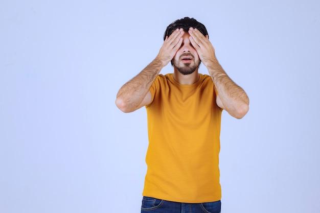 Mann im gelben hemd, das durch seine finger schaut.