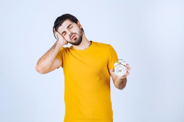 Mann im gelben hemd, das einen wecker hält und schläfrig aussieht.