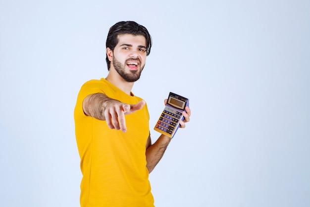Mann im gelben hemd, das mit taschenrechner arbeitet und wegen der ergebnisse glücklich aussieht.