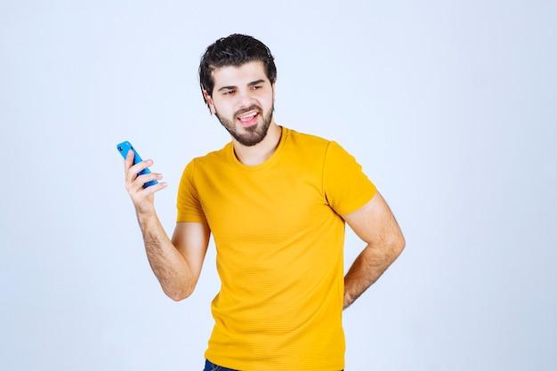 Mann im gelben hemd, das sein smartphone zeigt und es genießt.