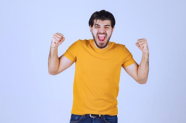 Mann im gelben hemd, das seine faust und kraft zeigt.