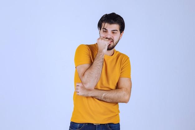 Mann im gelben hemd, das verführerische und ansprechende posen gibt.