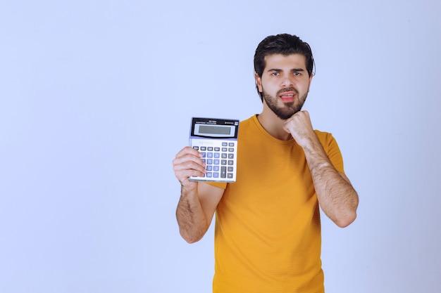 Mann im gelben hemd, der etwas auf dem taschenrechner berechnet.