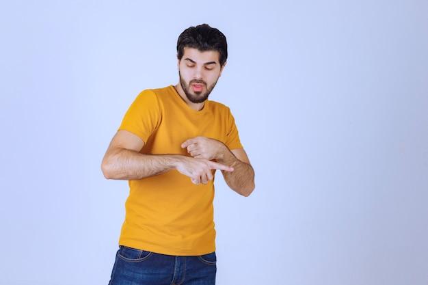 Mann im gelben hemd überprüft seine zeit.