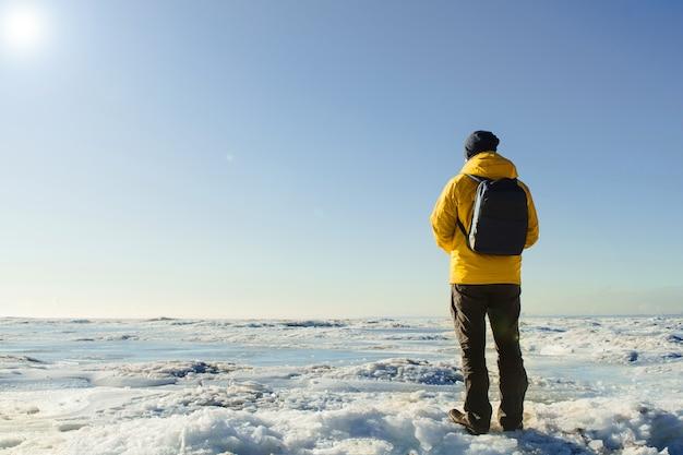 Mann im gelben regenmantel mit rucksack, der auf gefrorenem meer steht und weit schaut