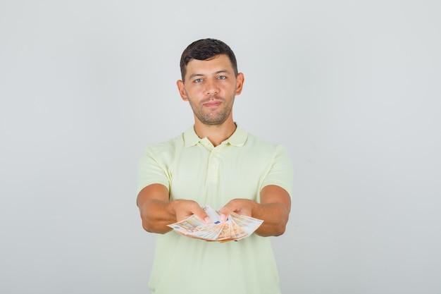 Mann im gelben t-shirt, das euro-banknoten hält